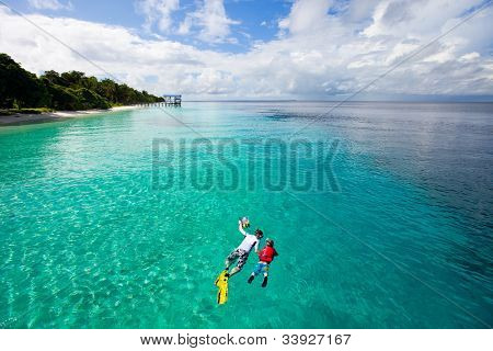 Father and son snorkeling in a tropical ocean