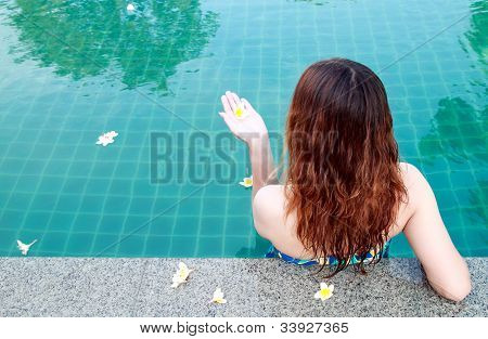 Beautiful Woman Resting On The Edge Of Swimming Pool