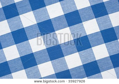 A blue, seamless, checkered picnic tablecloth fully framed with a diagonal perspective.