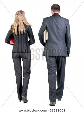 Back view of walking business team. Going young couple (man and woman) with books. beautiful girl and guy  together. Rear view people collection backside view of person. Isolated over white background