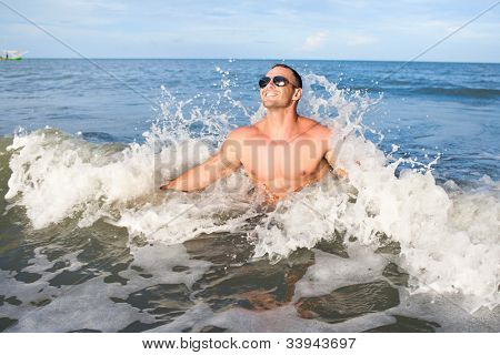 Happy young muscular male enjoying the sea