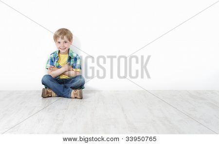 Handsome Little Boy Sitting On Floor