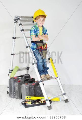 Little Boy Handyman With Helmet And Tool Belt On Stepladder