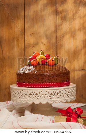 Christmas fruit cake decorated with marzipan fruits on cake stand