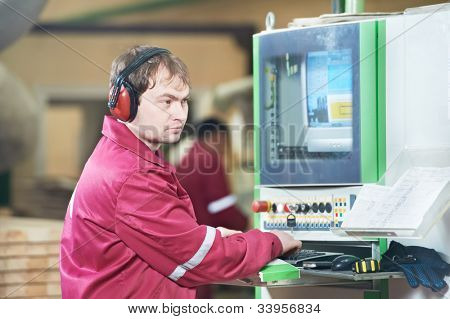 Portrait of young positive carpentry worker in front of furniture manufacture production at CNC wood cutting machine