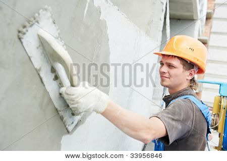 builder worker plastering facade of high-rise building with putty knife