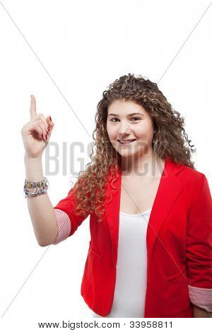 Cute teen girl over white background pointing to white space.