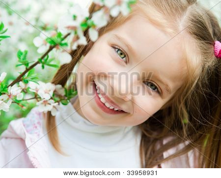 The beautiful little girl with bush blossoming tree