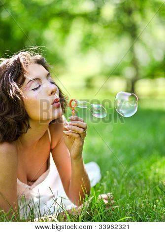 romantic young girl inflating colorful soap bubbles in summer park