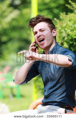 Young Man In The Park Talk On Telephone