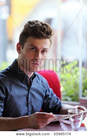 Young Handsome Man In Restaurant Looking At Menu