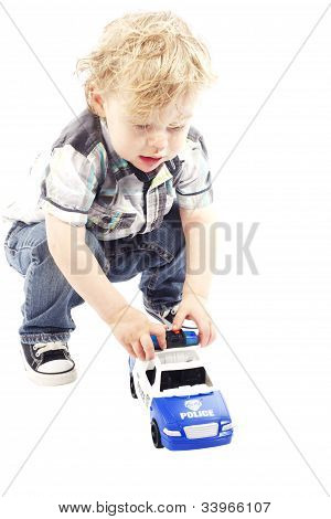 Cute Little Boy Smiling And Playing With Police Car