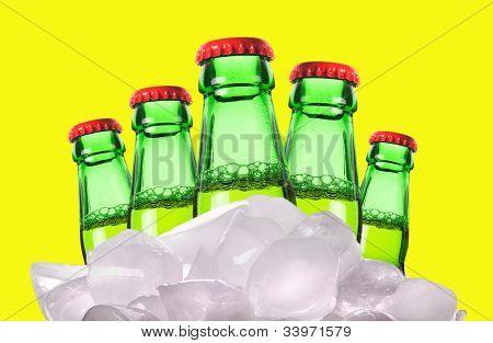 Botellas de cerveza con hielo sobre un fondo amarillo