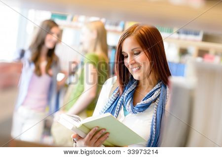 Teenage woman reading book studying among library shelves