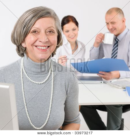 Business team happy senior businesswoman with attractive colleagues looking file