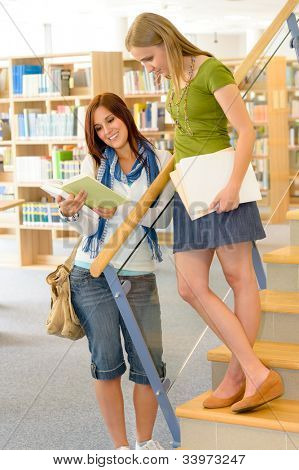 Two female students standing and reading book on library stairs
