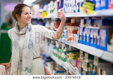 Bella joven de las compras de productos lácteos en una tienda de alimentos/supermercado (imagen de tonos de color)
