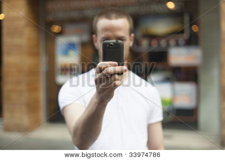 Men on street photographing with smartphone, background is blured city