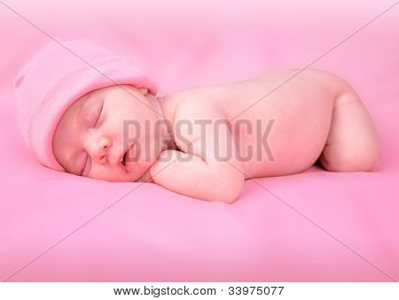 Little Baby Sleeping on Pink Bed with Hat