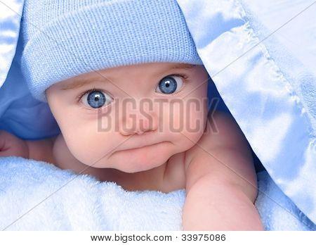 Bebezinho menino deitado sob o cobertor azul