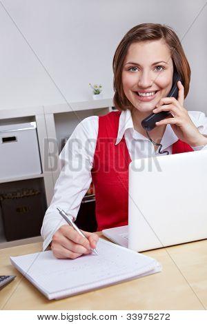 glückliche Frau arbeiten für Call Center Hotline Notizen während eines Telefonats