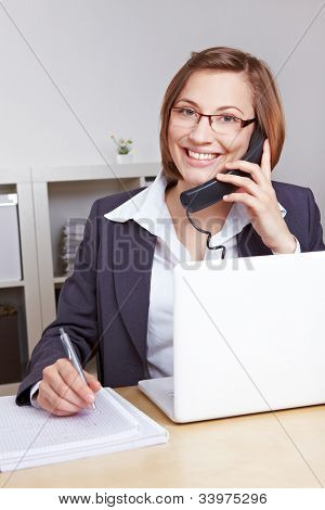Smiling business woman sitting at her desk in the office talking on the phone