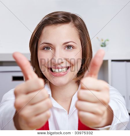 Happy business woman cheering with her two thumbs up in the office