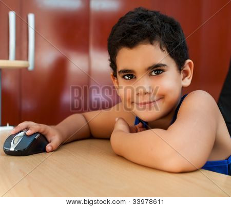 Latin boy working with a computer and smiling