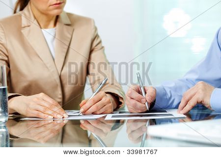 Business partners taking notes at seminar or meeting