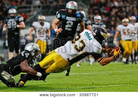 INNSBRUCK, VIENNA - JUNE 18: WR Danilo Naranjo Gonzalez (#23 Adler) is tackled by WR Talib Wise (#4 Raiders) on June 18, 2012  in Innsbruck, Austria. The Swarco Raiders beat the Berlin Adler 27:12.