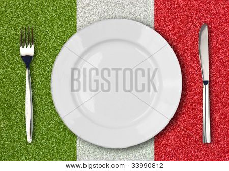 White plate, fork and knife top view on italian flag plastic table