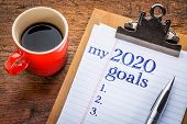 my 2020 goals list on clipboard and coffee against grunge wood desk, New Year resolutions concept poster