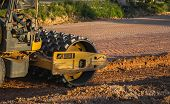 Soil Compactor With Vibratory Padfoot Drum. Heavy Duty Machinery Working On Highway Construction Sit poster