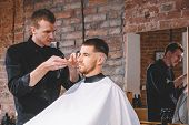 Young Male Barber Shaves The Clients Head With A Electric Trimmer. Young Bearded Man Getting Haircut poster