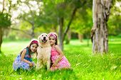 picture of hug  - Two young girls hugging golden retriever dog in the park - JPG