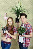Happy couple with domestic flowers looking at camera poster