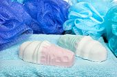 Two ice cream scented bathwater additive salts on blue towel with shower poufs.