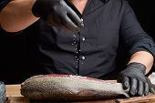 Chef In A Black Shirt And Black Latex Gloves Prepares Salmon Fillet On A Wooden Cutting Board, Proce poster