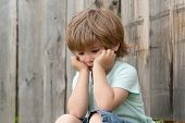 Sadness. Sad Boy. A Lonely Child Sits Near A Wooden Fence. Frustration. Sad Emotions. Experiences. C poster