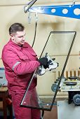 image of suction  - glazier worker with suction cup holding glass at double glazing window manufacture - JPG