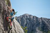 Rock Climbing And Mountaineering In The Paklenica National Park. A Woman Overcomes A Challenging Cli poster