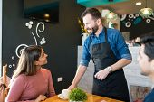 Mid Adult Waiter Serving Coffee To Female Customer At Restaurant poster