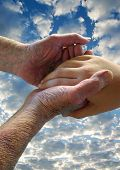 stock photo of healing hands  - A ninety-year-old man cradles the hand of a young girl against a summer sky.