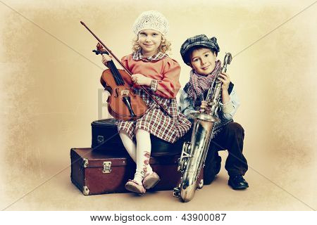 Cute little boy with his old saxophone is sitting on a suitcase with charming little lady violinist. Retro style.