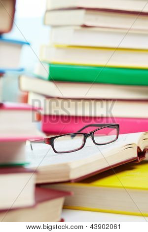 Vertical image of eyeglasses lying over opened book in the library