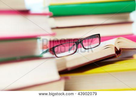 Imagem de close-up de óculos entre pilhas de livros