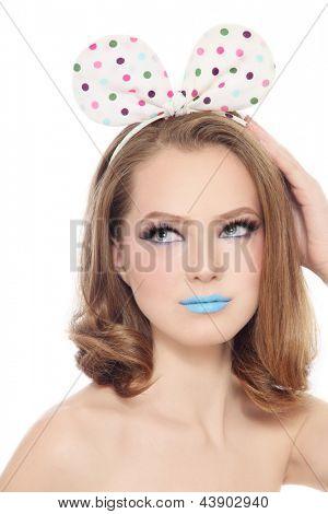 Pretty girl teen com maquiagem extravagante e curva de bolinhas engraçadas na cabeça olhando para cima, branco backg