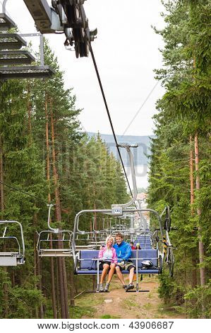 Young couple sitting on chair lift traveling through forest