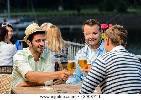 Tres amigos varones relajación noche bebiendo cerveza terraza del restaurante