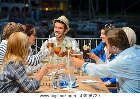 Group of young friends clinking their glasses celebrating night out